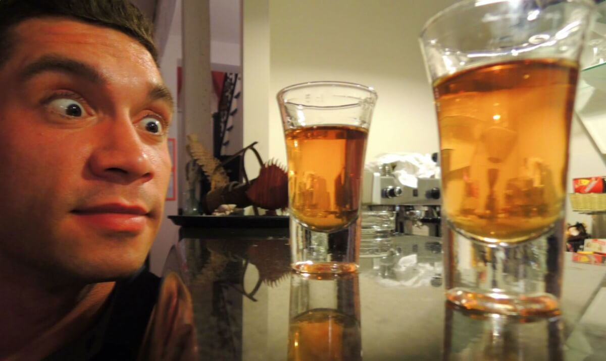 a man looking at two glasses of supreme rakija